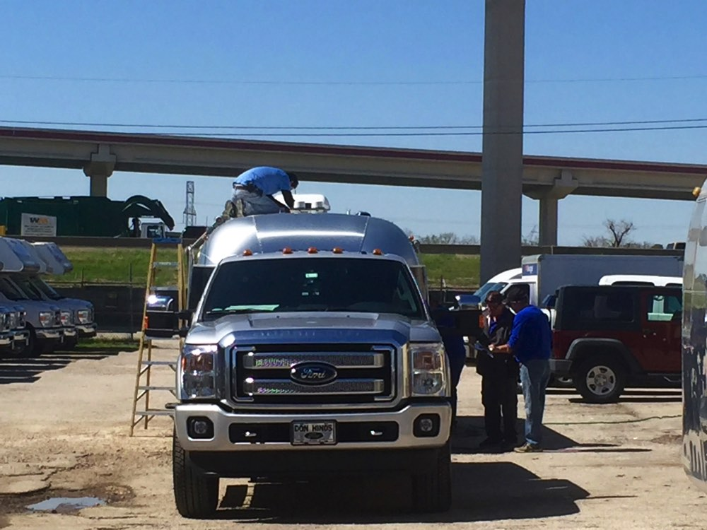 caulking the seam on top of the June Bug]  [caption: North Dallas RV repairs lots of old Airstreams