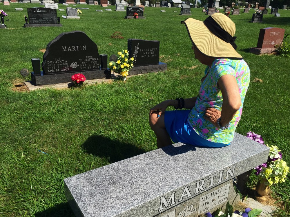 "Lynne always wants to ""visit Mom and Dad and Mike"", and we're thankful she can't read, because her own headstone is in place there. But isn't this a sweet photo of her?"